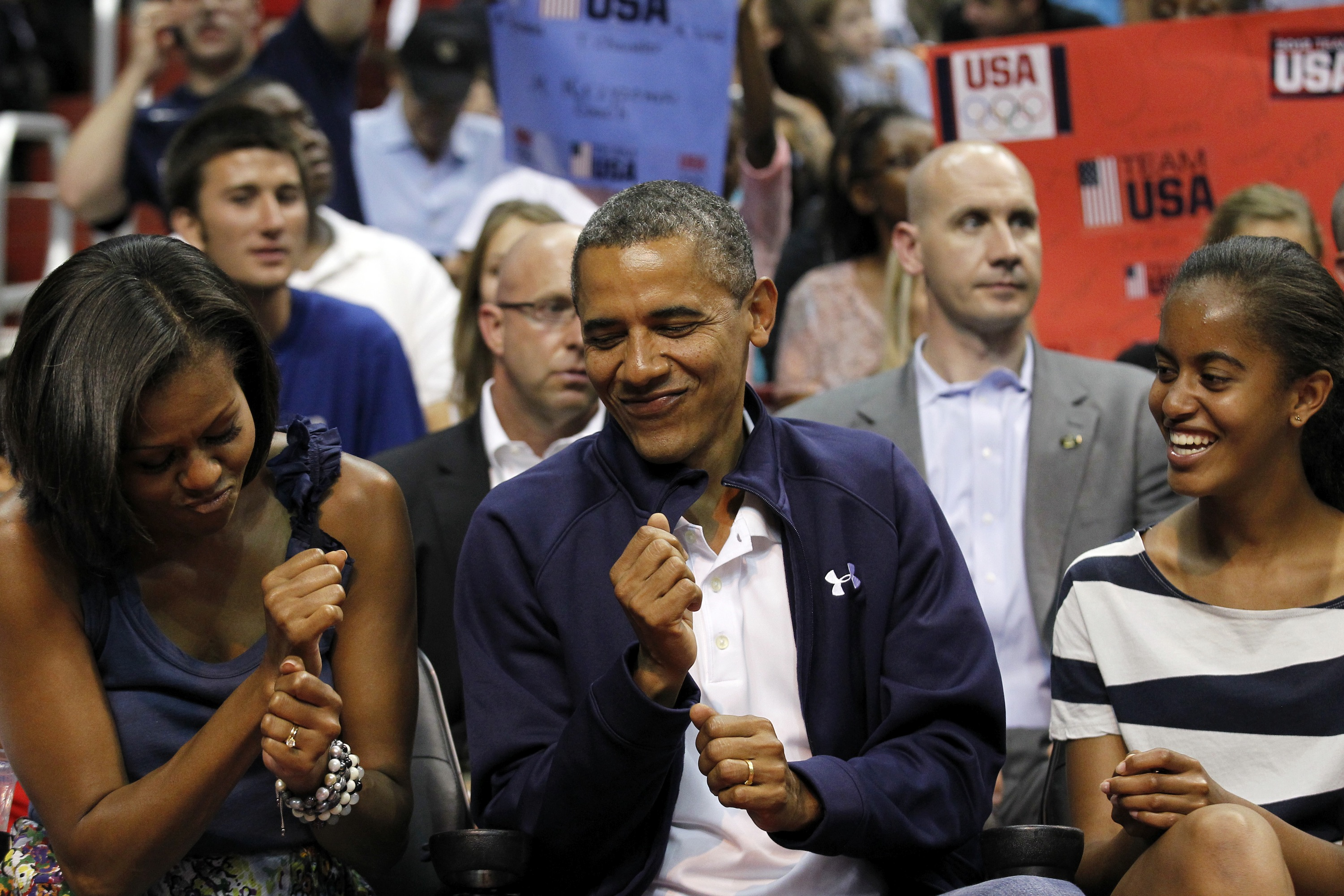 President Barack Obama dances to the music with first lady Michelle Obama, with daughter Malia Obama, right, while attending Team USA and Brazil in an Olympic men's exhibition basketball game, Monday, July 16, 2012, in Washington. Team USA won 80-69. (AP Photo/Alex Brandon)